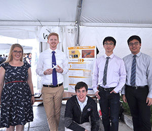 Five students -- membes of Team Fat Thunder - stand in front of their poster