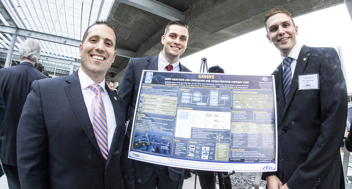 Steven Chetcuti,and two other grad students who worked on the ASSIST project stand in front of poster