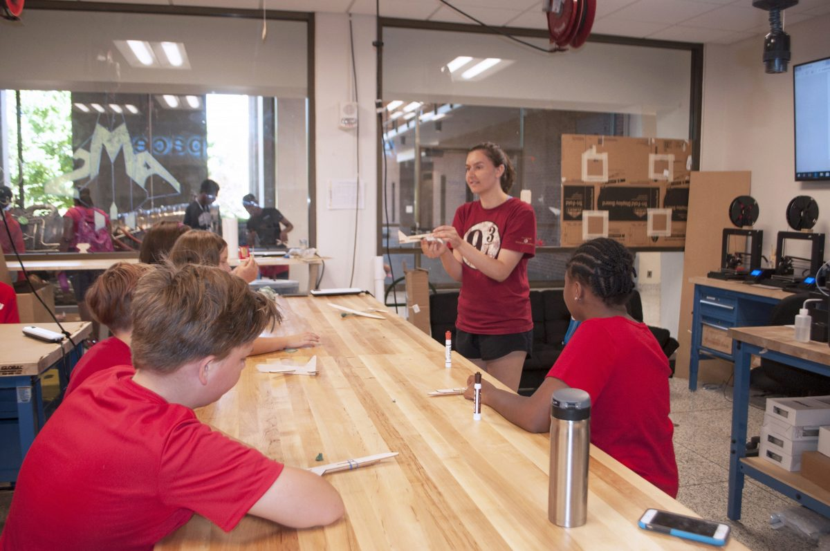 Julia Filloon instructs the students on how to make a balsa glider