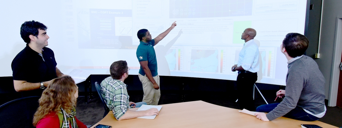 Students gathered around a white board discussing research