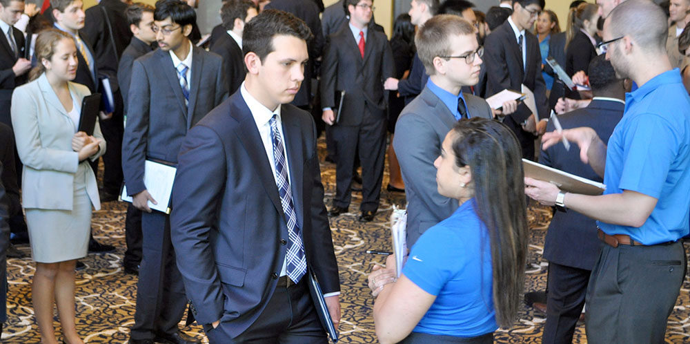 male student talking with a recruiter in crowded room where the Career Fair is happening