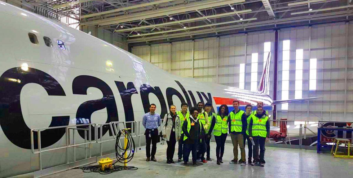 A group of 11 students next to a Cargolux plane. Seen of the students are wearing bright green safety vests