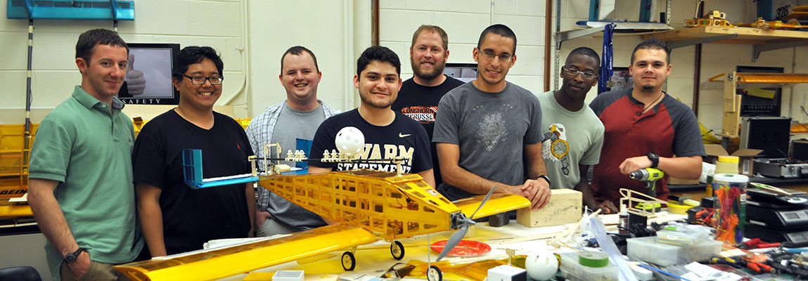 Team of AE students in their lab with their remote control plane, Buzz Killington, that won third place in the 2015 AIAA Design Build Fly competition.
