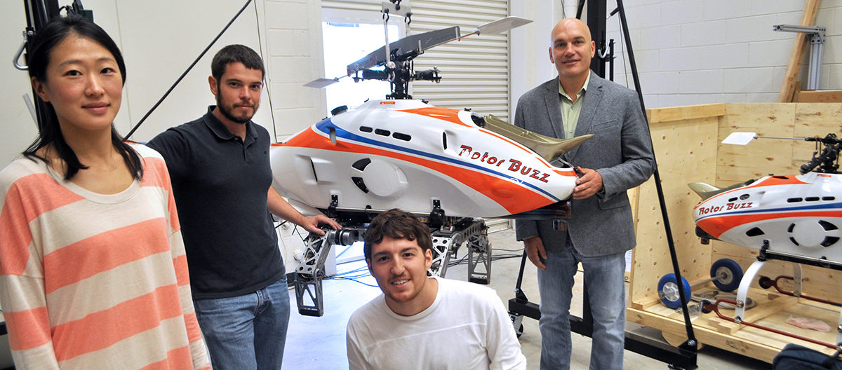 Three students join Dr. Mark Costello in the CAMM Lab where they surround a UAV that they are getting ready to test