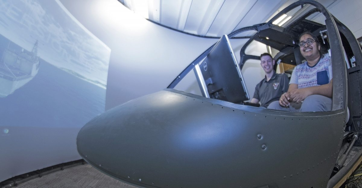 Bob Walters and Vinodhini Comandur sitting in the helciopter simulator