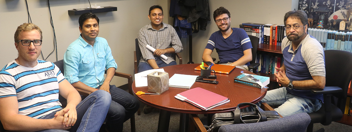 Four grad students around a table with their advisor, Prof. Suresh Menon