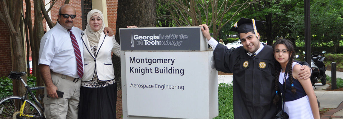 An international student graduate and his family standing next to the Montgomery Knight Building sign.