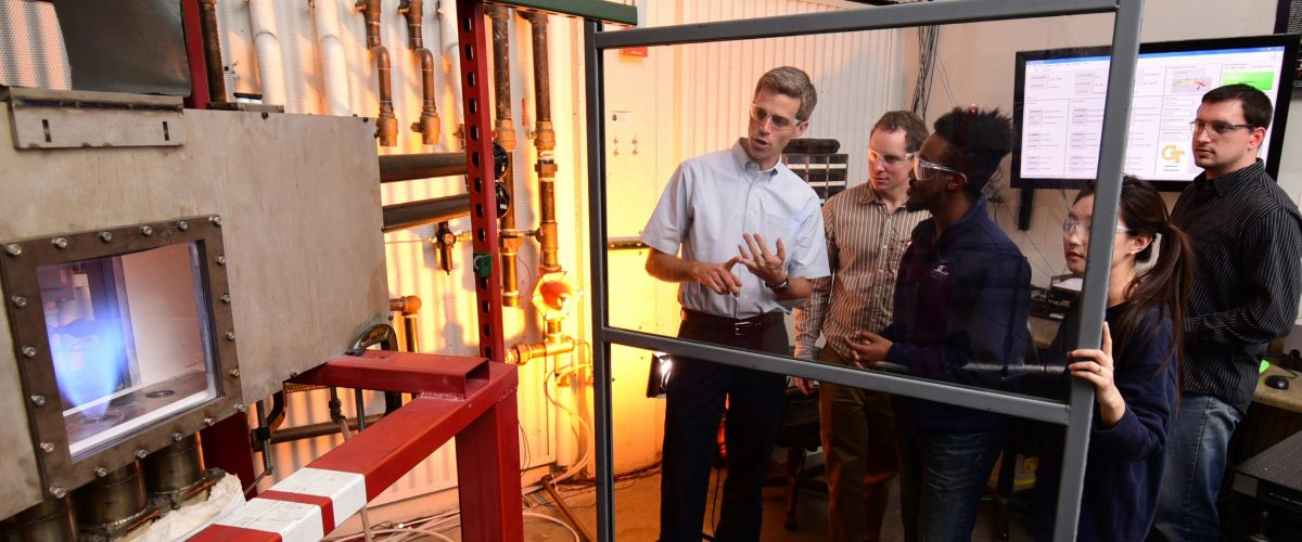 Prof. Lieuwen explaining some combustion equipmen to a group of three grad students