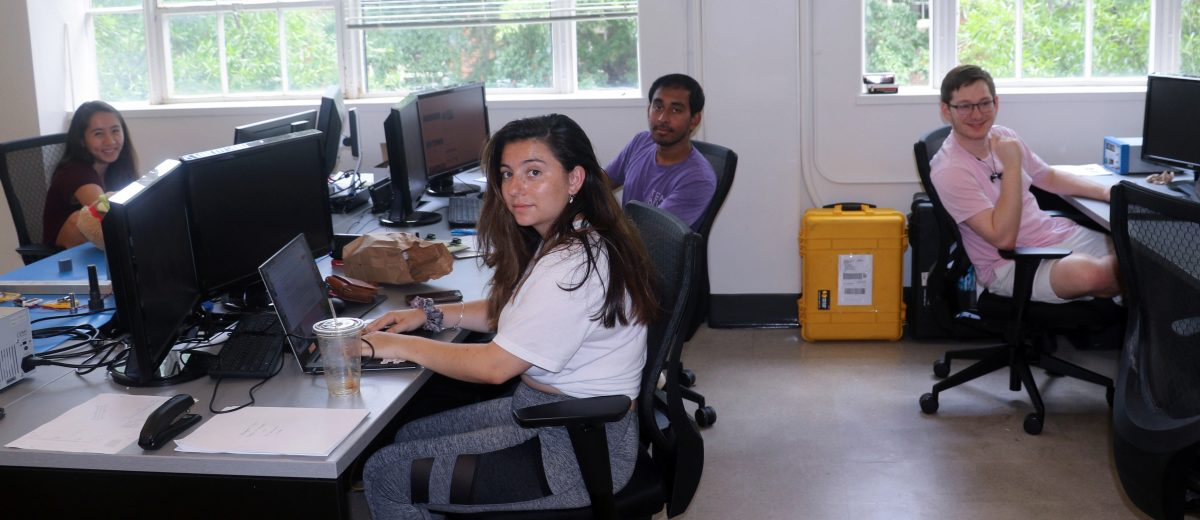 Five grad students from Prof. LIghtsey's lab working at their computers