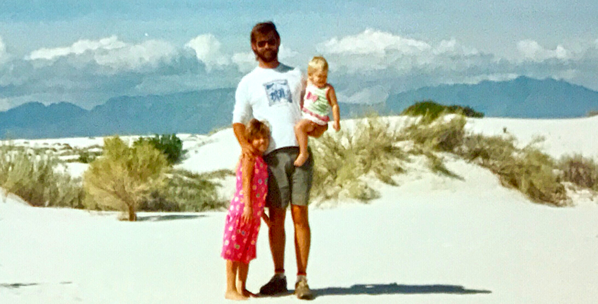Mariah Amstutz as a toddler, being held by her father, Ronnie on a beach. Next to them is Mariah's sister, Stacy