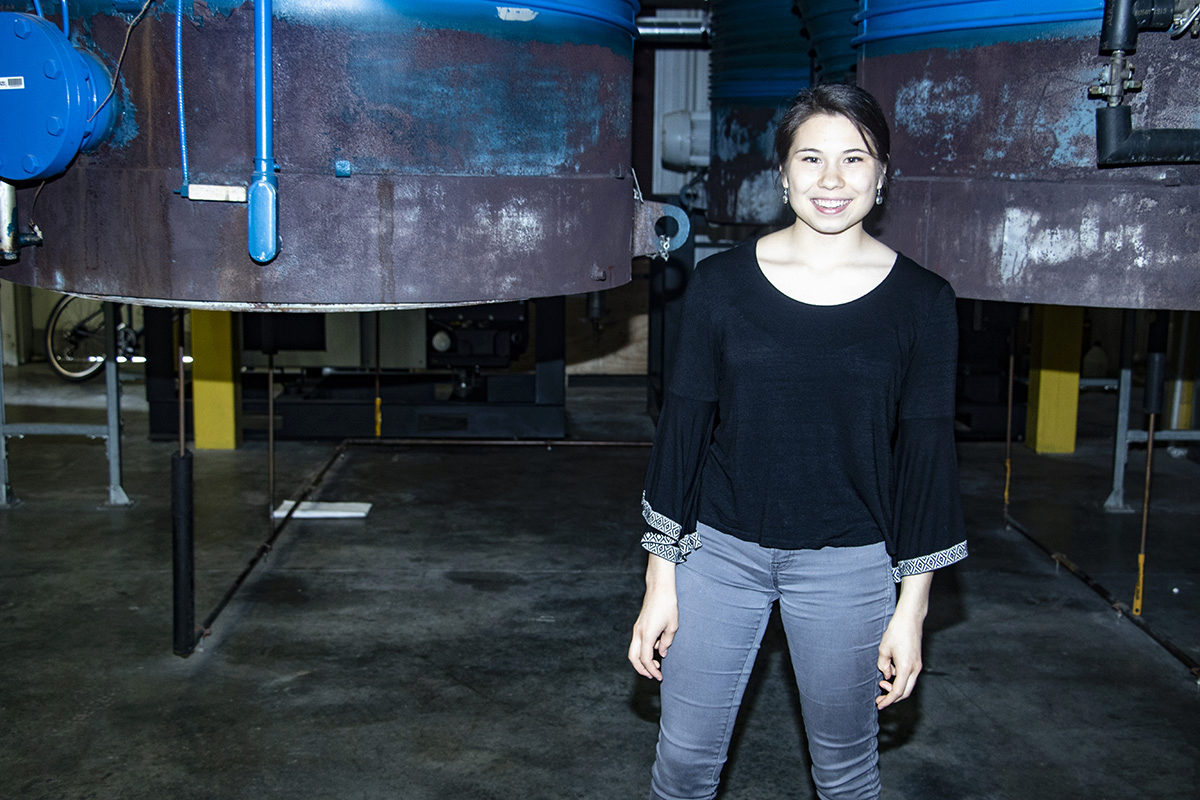 Abigail McClain standing in front of one of the vacuum chambers at the HPEPL