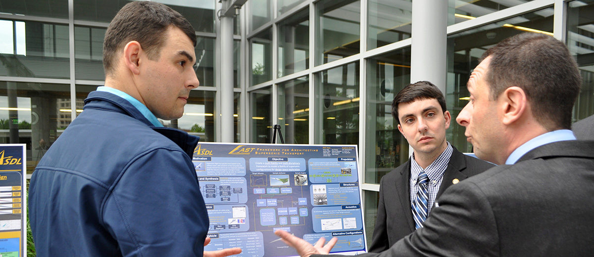 two students talking with an industry sponsor in front of their poster during the ASDL Grand Challenge revea;