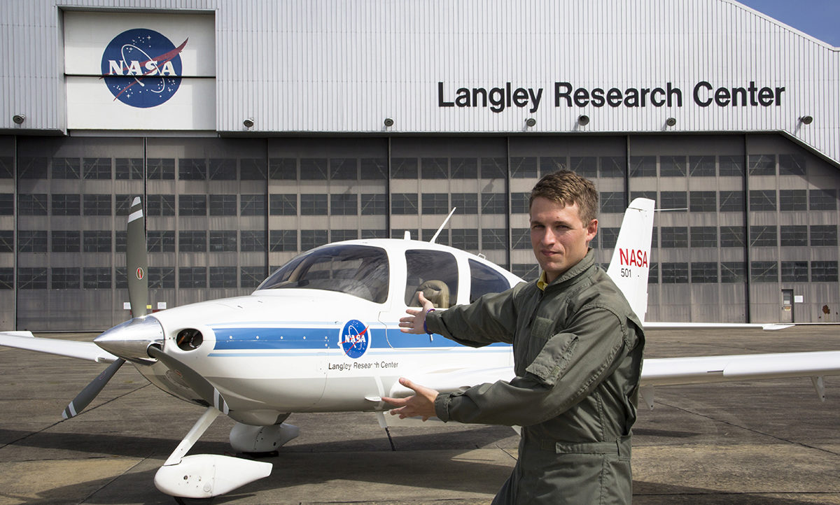 Kenneth Smith in front of the Langley Researach Center, pointing dramatically to an airplane he's been working on