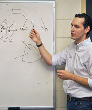 Professor Di Leo speaking about drawings on a white board