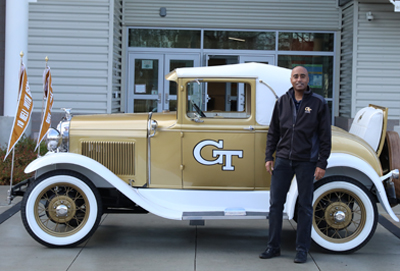 aerospace engineering professor Stephen Ruffin stands next to the Ramblin Wreck outside of the Tuskegee Airmen Global Academy