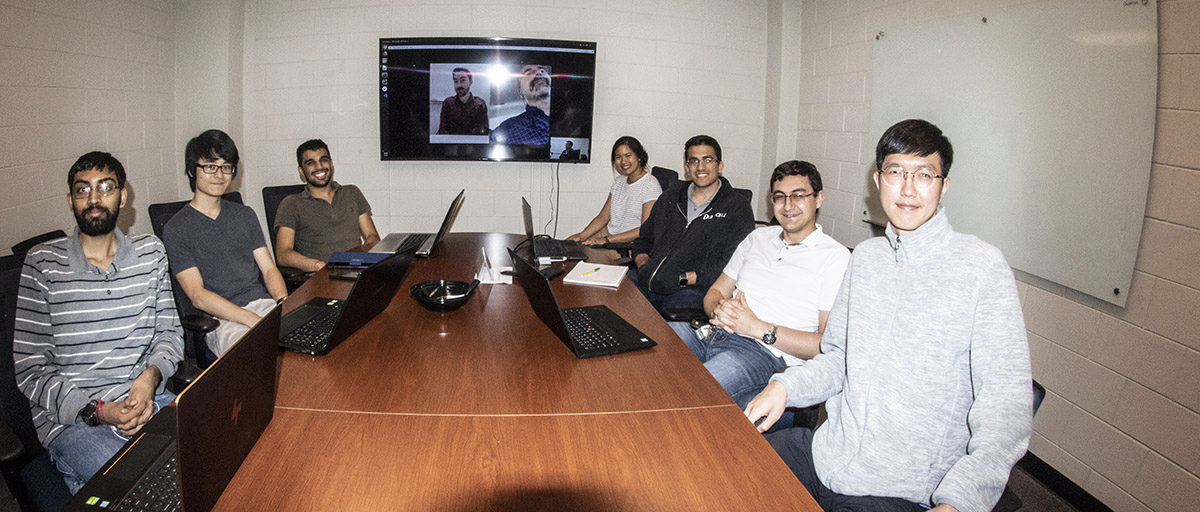Seven of the 10-member Icarus Team sitting at a conference table