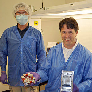 Dr. Brian Gunter and a student holdin g a prototype of the RANGE satellite