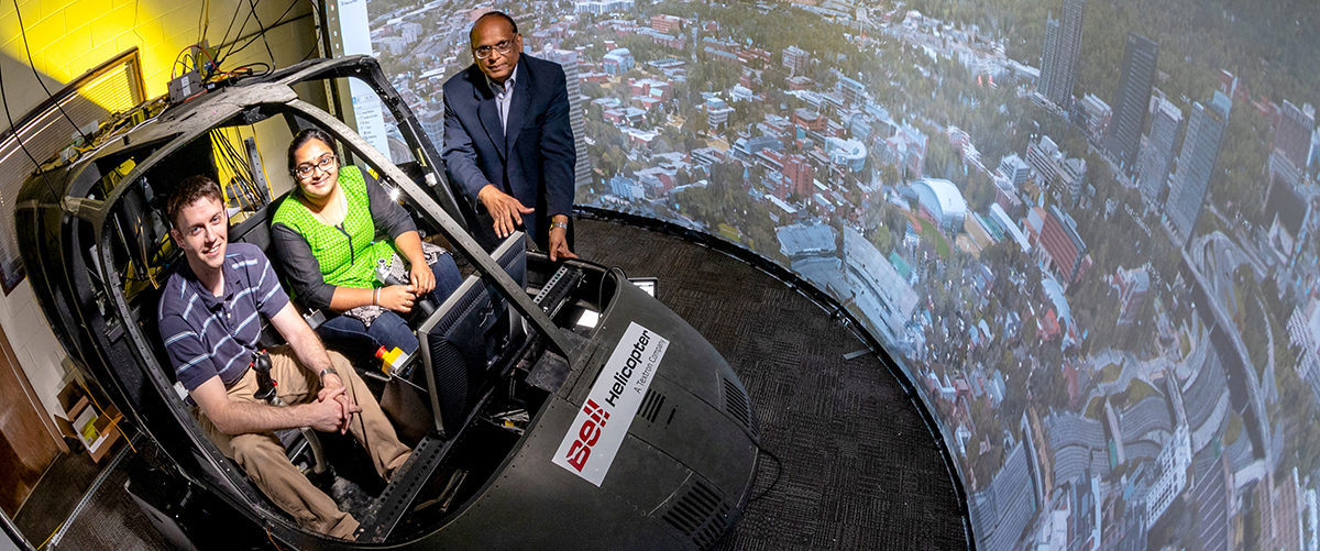 The Rotorcraft Sim Lab: Two graduate students sitting in the cab of Bell Helicopter with Prof. Prasad