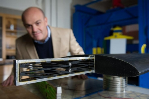 <p><em>Massimo Ruzzene, a professor in the School of Aerospace Engineering, designs metamaterials, which are synthetic composite structures with properties not found in materials derived from nature. Here he demonstrates a structure that could help reduce structural fatigue caused by continual flexing in aircraft wings. (Click image for high-resolution version. Credit: Rob Felt)</em></p>