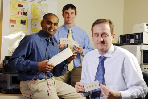 Graduate students Tushar Thrivikraman and Chad Patterson, and Georgia Tech professor John Papapolymerou (left to right), hold radar sub-arrays consisting of a flexible polymer substrate, silicon-germanium chips and other electronics. (Photo: Gary Meek)